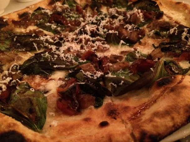 Pizza with pork belly and kale.